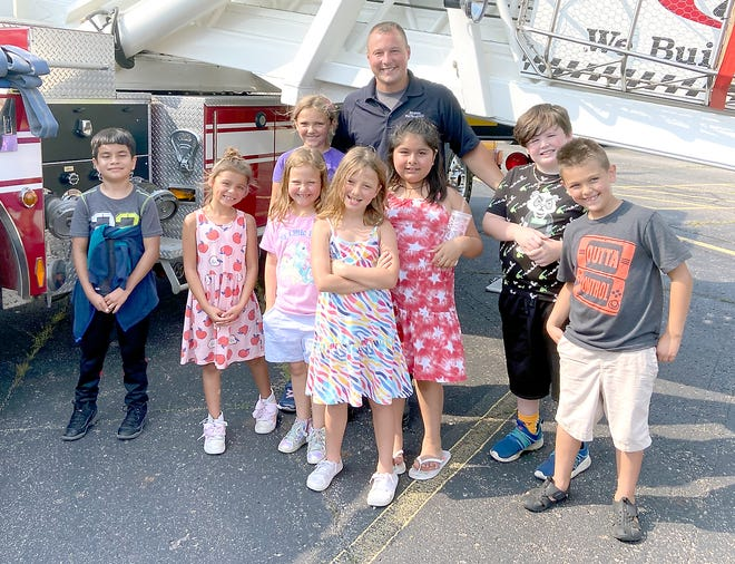 """Students got familiar with a ladder truck Wednesday, with guidance from firefighter Brandon Adamski, as part of """"Transportation Extravaganza."""""""