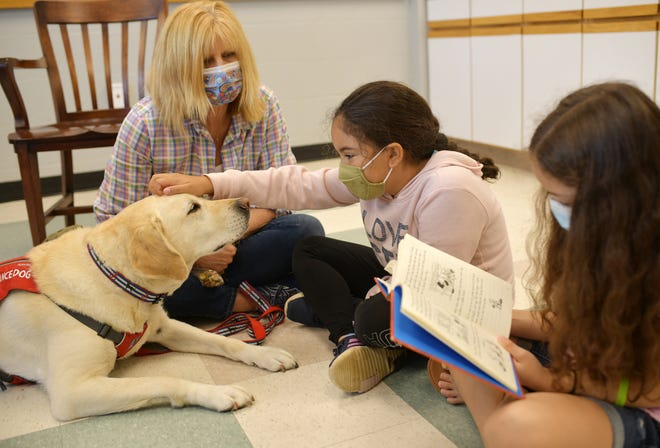 Cathy Zemaitis, director of development at NEADS, sits with Loring as Eva and Sierra read from a book at Girls Inc. of Worcester on Thursday. Three NEADS dogs come in every week for about an hour of literacy building to spend time with 45 girls for the Pawsitively Girls Summer Literacy Program.