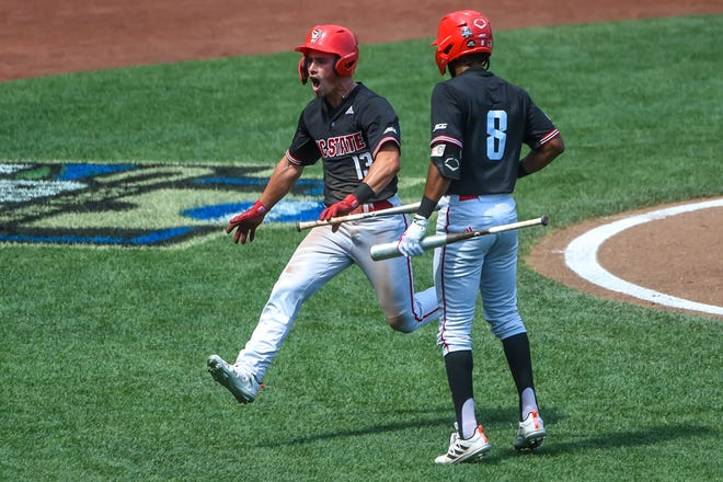 N.C. State Wolfpack utility Tyler McDonough (13) celebrates with infielder Jose Torres (8) after scoring in the ninth inning against the Stanford Cardinal at TD Ameritrade Park on Jun 19, 2021, in Omaha, Nebraska. Torres and McDonough both project as top-150 prospects in the 2021 MLB Draft, which begins Sunday.