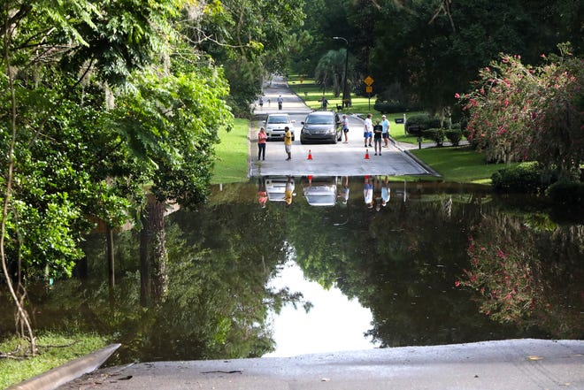 Residents of the Robin Lane neighborhood off NW 39th Ave. look over a flooded road that is the single exit to the neighborhood in Gainesville area after Tropical Storm Elsa.