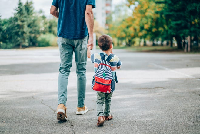 A father walks his son to school.