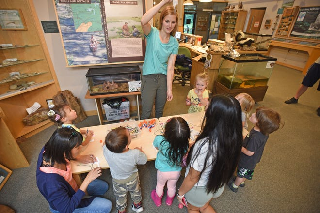 Chelsea Gottfried, preschool teacher and naturalist at Lowe -Volk Park, shows children how to make a woodpecker on a string Thursday morning. The Nature Storytime program continues every Thursdays in July at the Lowe-Volk Park.