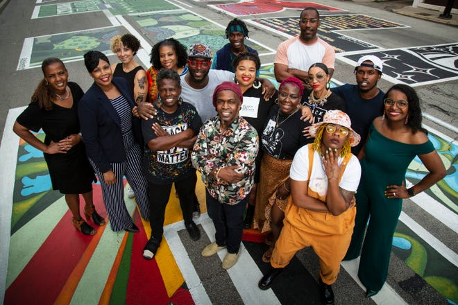 Alandes Powell (far left), of Black Art Speaks, poses with a group of the artists who contributed to the Black Lives Matter mural painted in front of City Hall in downtown Cincinnati last year.