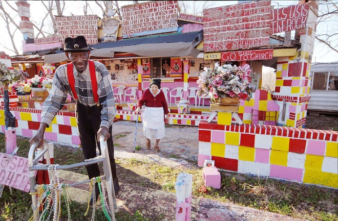 """Reverend H.D. """"Preacher"""" Dennis and his wife Margaret in front of her store Margaret's Grocery in Vicksburg, Mississippi.  In it's heyday the site became a must-see piece of roadside folk art. (Courtesy Mississippi Folk Art Foundation)"""