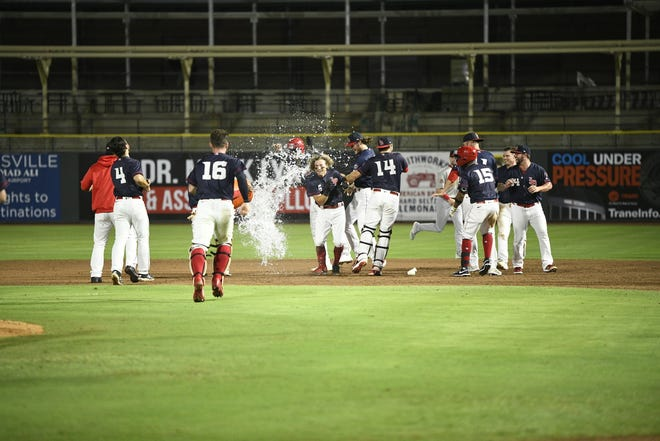 TJ Friedl (center, facing camera) hit a walk-off single for the Louisville Bats in the bottom of the 10th inning on Wednesday at Slugger Field. The Bats beat Memphis 4-3.