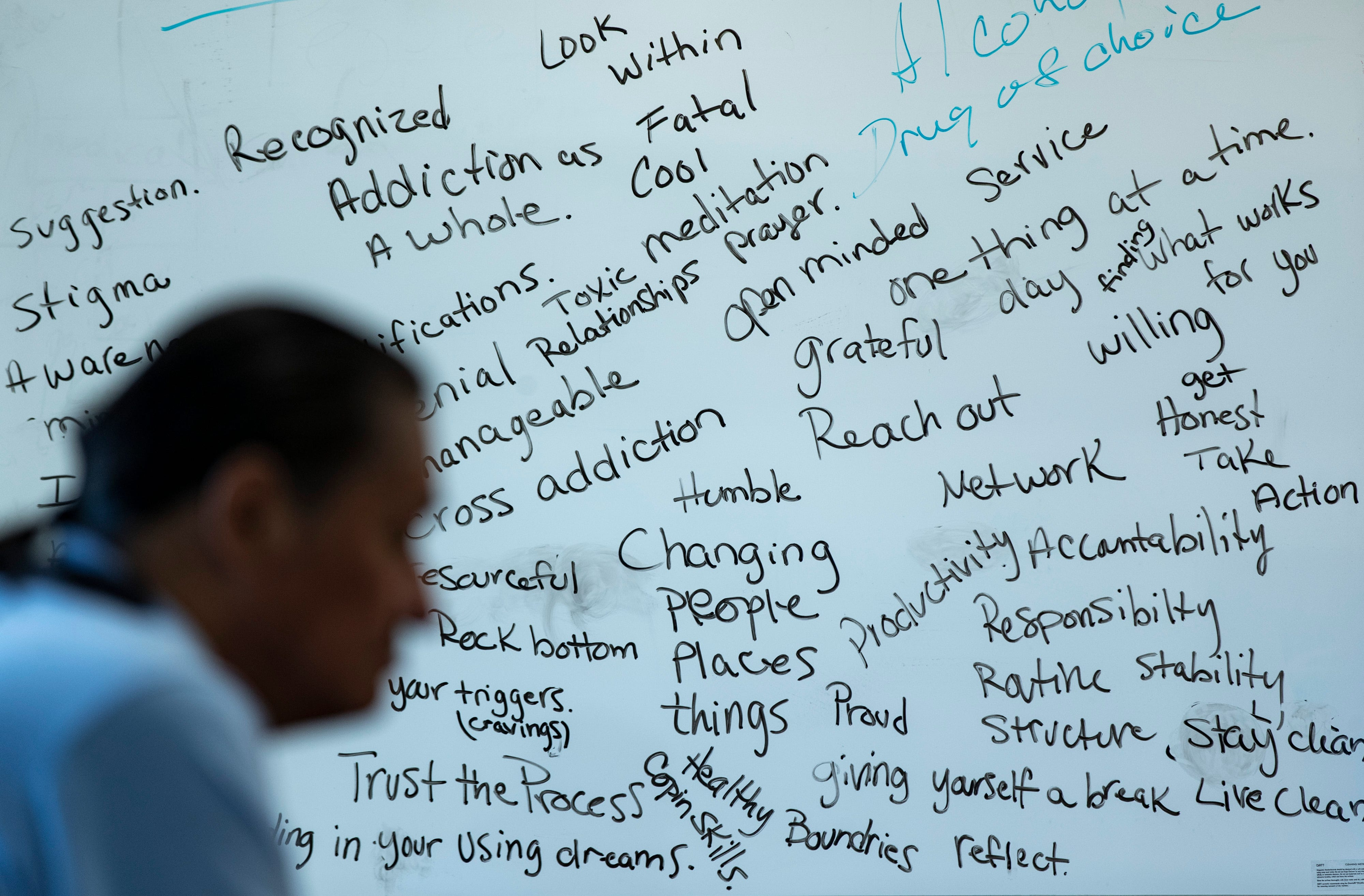 A group session participant looks on in front of a marker board covered in topics and phrases from group sessions at the Good Road Recovery Center in Bismarck, North Dakota. June 21, 2021