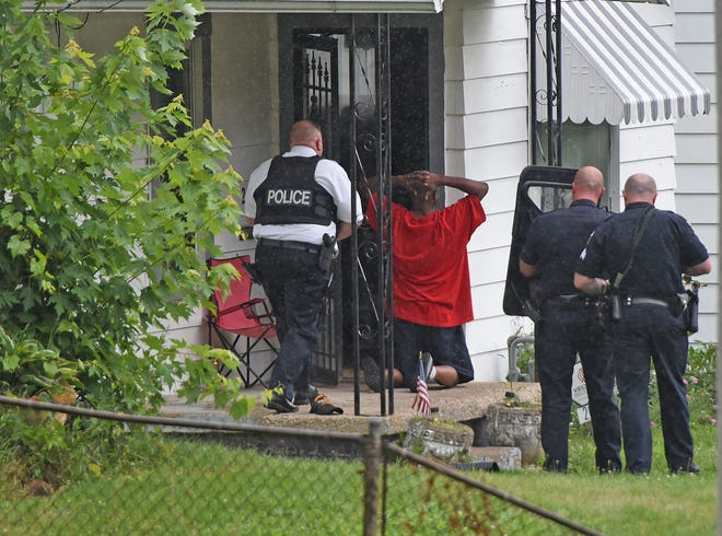 Mansfield police officers take a man at 261 East Arch street into custody after a standoff on Thursday.