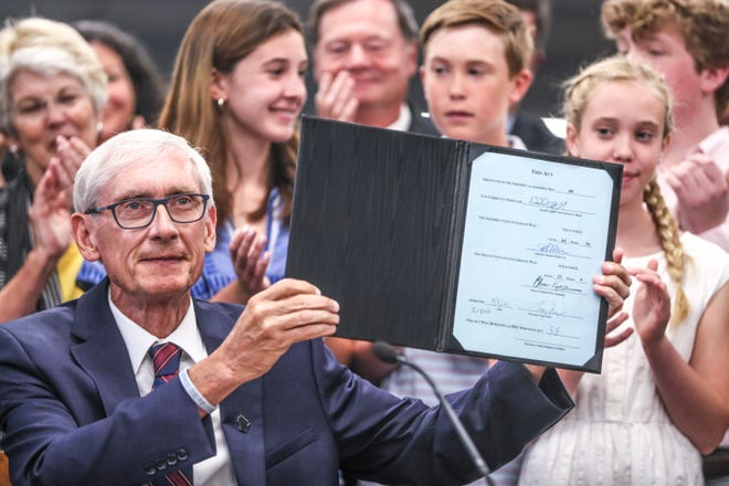 Gov. Tony Evers shows the 2021-23 biennial budget now known as 2021 Wisconsin Act 58 after signing it Thursday, July 8, 2021, at Cumberland Elementary School, 4780 N. Marlborough Drive, in Whitefish Bay. The bill provides one of the largest tax cuts in Wisconsin's history. Evers also announced $100 million in new funding for public schools in the biennial budget.