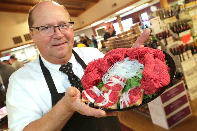 Ray's Butcher Shoppe co-owner Perry Podd holds up the cannibal sandwich, made from raw beef and onions on rye bread, at Ray's Butcher Shoppe in Greenfield. The shop has been around since 1977.