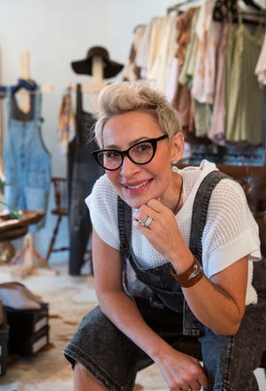Carri Luden, owner of Urban Threads, sits amongst the displays  of clothes and apparel for sale in the Urban Threads store in Heath, Ohio on July 8, 2021.