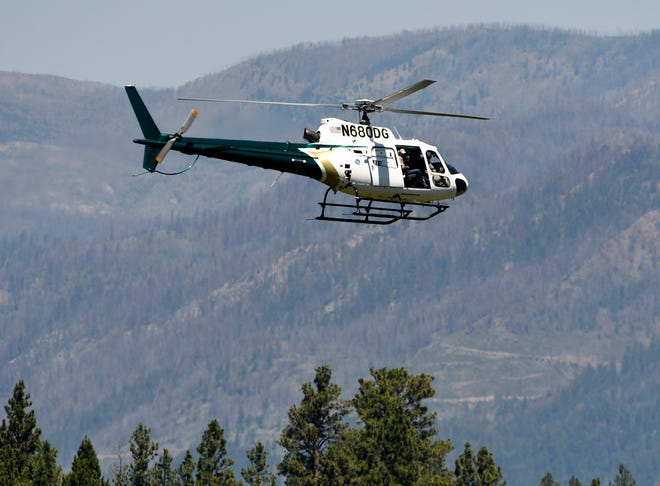 A helicopter from Montana Fish, Wildlife and Parks flies around the Ovando, Mont., area on Tuesday, July 6, 2o21, in search of a bear that killed a camper early that morning. The search for the bear continued Wednesday.