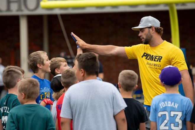 Dallas Goedert high fives a youth football player at the Sanford Power football camp July 7 in Brookings