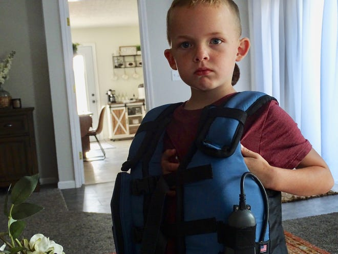 Conlee Handshy, 6, shows off his AffloVest used for his cystic fibrosis treatments. The vest is portable and allows him to move around and even go out while he's receiving his CF treatments.