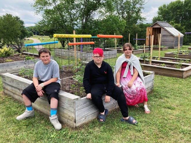 Zanesville City Schools students Charles Bittner, left, Haylie Eldridge and Taylor Daw sit on a planter of tomato plants Thursday in the community garden behind Zane Grey Intermediate School. The students are part of the school's summer school program that used gardening to integrate science and language arts with hands-on teamwork. The program was open to all students in the district.
