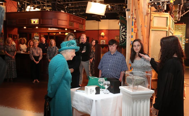 """The Queen met cast and crew during a visit to the set of longtime TV series """"Coronation Street,"""" including entering the Rovers Return pub on the set, on July 8, 2021 in Manchester."""