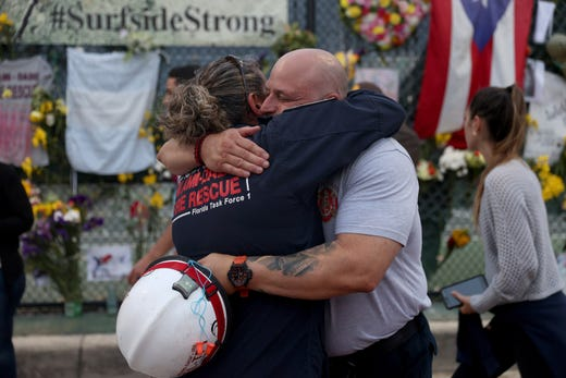 Search and Rescue personnel Maggie Castro (L) and Eddy Alarcon hug as they visit the memorial to the victims in the collapsed 12-story Champlain Towers South condo building as the search and rescue efforts are reported be transitioning to a recovery operation on July 7, 2021 in Surfside, Fla.