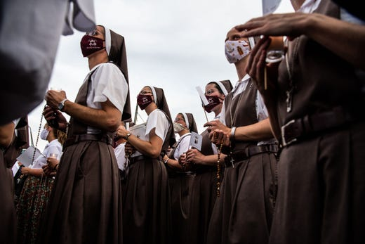 """Nuns from the St. Josephs Catholic Church pray at the """"Surfside Wall of Hope & Memorial"""" near the site where a building collapsed in Surfside, Fla. on July 7, 2021."""