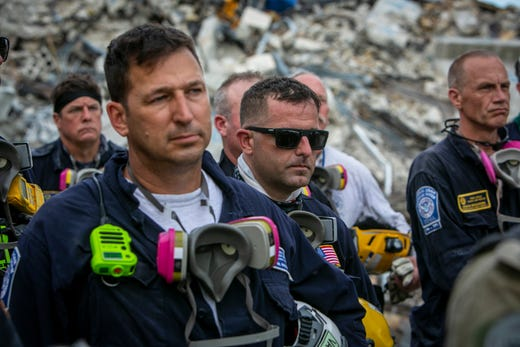 Members of a search and rescue team stand in front of the rubble that once was Champlain Towers South during a prayer ceremony in Surfside, Fla., Wednesday, July 7, 2021.