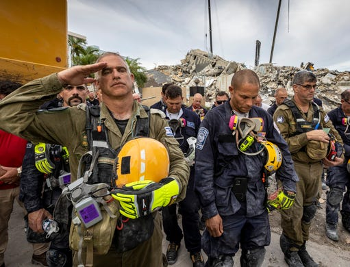 A member of the Israeli search and rescue team, left, salutes in front of the rubble that once was Champlain Towers South during a prayer ceremony, Wednesday, July 7, 2021, in Surfside, Fla. Members of search and rescue teams and Miami-Dade Fire rescue, along with police and workers who have been working at the site of the collapse gathered for a moment of prayer and silence next to the collapsed tower.
