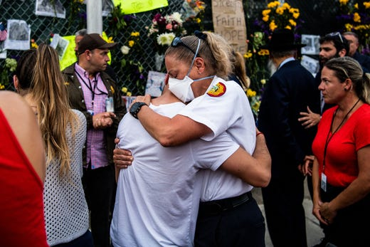 """A member of the Miami-Dade Fire Department hugs a family member of the victims at the """"Surfside Wall of Hope & Memorial"""" near the site where a building collapsed in Surfside, Fla. on July 7, 2021."""