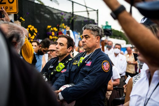 """Members of the Miami-Dade Fire Rescue visit with family members and friends of the victims at the """"Surfside Wall of Hope & Memorial"""" near the site where a building collapsed in Surfside, Fla., north of Miami Beach on July 7, 2021."""