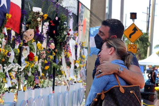 Laura Solla weeps as she and William Chamak, both of Argentina, visit the memorial wall dedicated to those lost in the Champlain Towers South condo collapse in Surfside Fla., July 8, 2021. The couple had several friends that were killed in the condo collapse.