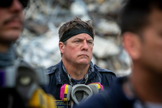 A member of a search and rescue team stands in front of the rubble that once was Champlain Towers South during a prayer ceremony, Wednesday, July 7, 2021, in Surfside, Fla.