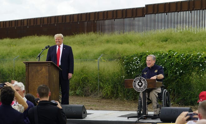 Former President Donald Trump, left, and Texas Gov. Greg Abbott, right, visit an unfinished section of border wall in Pharr on June 30. [AP PHOTO/ERIC GAY]