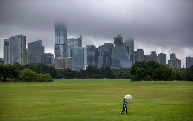 Daniella Bogorad and her cousin Romina Torio walk across a soggy Great Lawn at Austin's Zilker Park on Friday, when nearly a quarter-inch of rain was recorded in the city. Showers in the first nine days of July have dropped 3.37 inches of rain. July normally gets 1.96 inches for the whole month.