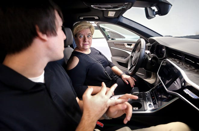 Lynnie Goss goes over the features of her new Audi A6 with Technologist Chris Reimenschneider on Thursday at Audi Cuyahoga Falls. Goss, who lives in Columbus, made the drive to Cuyahoga Falls to pick up the car that was delivered from Austin, Texas.