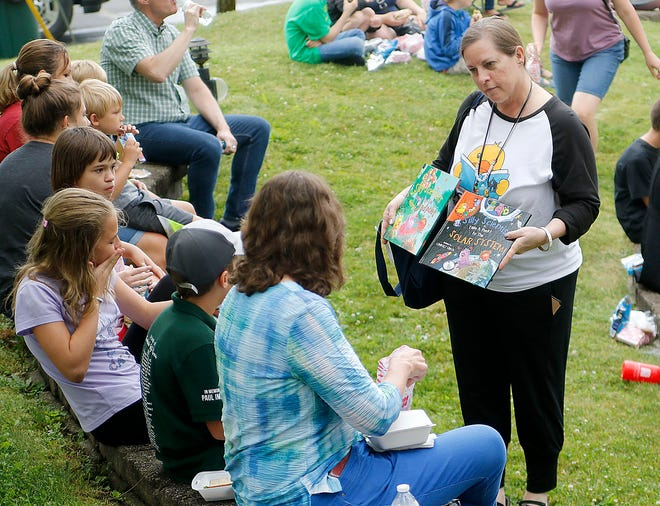 Ashland Public Library's Laura Humrichouser passes out free books to the youth at the United Way of Ashland County's Fun Friday's at Corner Park. TOM E. PUSKAR/TIMES-GAZETTE.COM