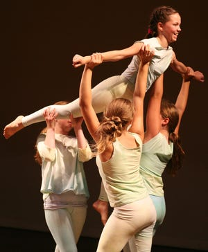 Students in a past year's Kid's Co'Motion program perform a lift. The workshop teaches kids skills, such as creative and critical thinking, teamwork,and dance technique.