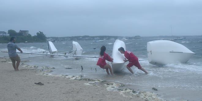 Town of Barnstable's beach safety officer Sanjeev Kc, left, helps lifeguards push ashore four sailboats that blew off their float onto Veteran's Beach this morning as Tropical Storm Elsa blew over, bringing rain and wind gusts to 50 miles an hour.