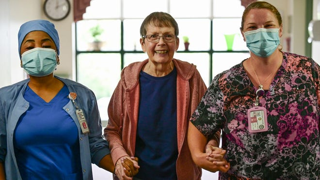 Certified nursing assistants Naomi Sirleaf, left, and Meredith Cacciotti, right, assist resident Mary Callahan as she takes a walk at Neshaminy Manor in Doylestown Township. The county is looking to hire more nursing staff members.