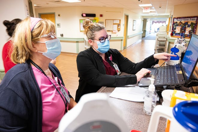 Registered nurse Kathi Reilley (left) and Erica Malliaris, a licensed practical nurse, look over computerized patient records at Neshaminy Manor, the county's nursing home in Doylestown Township.  The home will host a career fair for nurses on Wednesday.