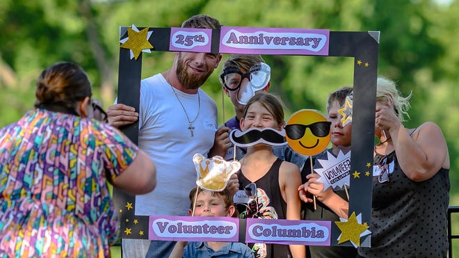 Katherine Wortmann, left, takes a photo of the Crickett family at a photo booth during the Columbia volunteer picnic Thursday at Stephens Lake Park.