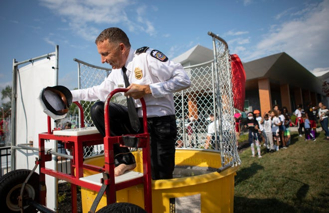 Columbus police Deputy Chief Timothy Becker climbs out of the dunk tank Friday after being submerged by a young hurler during a summer block party outside the Linden Community Center, hosted by the bicycle officers of the Safe Streets program in partnership with The Starfish Assighment.