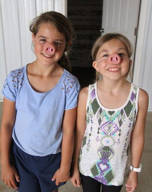 Abby Behm and Athea Bingham, both from Fosston and both 8 years old, show off the pig noses they got from the Barrick Family Farms trailer at the Polk County Fair.
