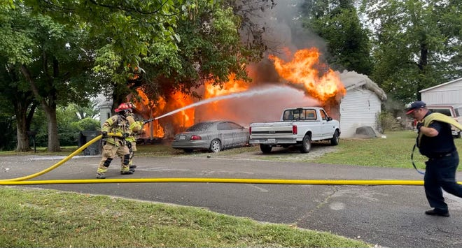 Columbia Fire & Rescue Firefighter Carter Prescott hoses down a house fire on Rinks Court as Eric Nieble assists in the Riverside neighborhood of Columbia, Tenn., on Friday, July 9, 2021.
