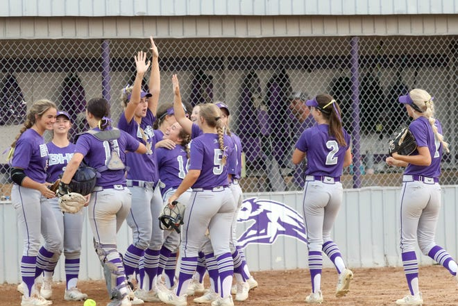 Burlington Grayhounds' Megan Topping, arms raised, celebrates with her teammates after winning 9-0 against the Fort Madison Bloodhounds in a Class 4A regional quarterfinal Thursday at Wagner Field in Burlington.
