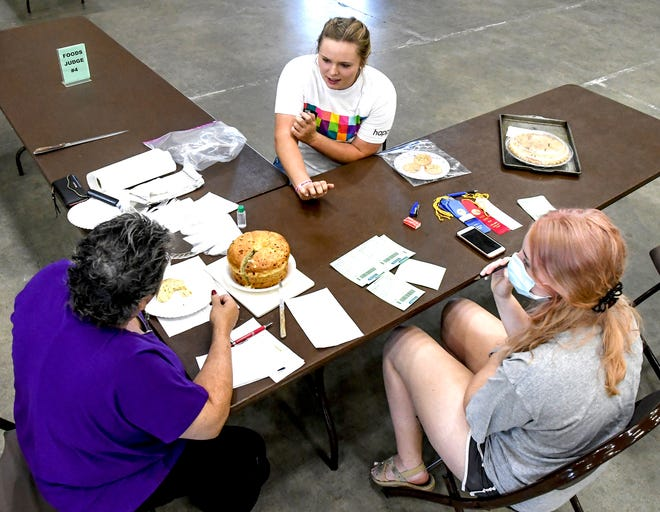 Katie Mongeau, center, describes how she made a cake during a 4-H foods consultation judging session in the exhibition building during the 2020 Finney County Fair. Social distancing was used during judging of various categories. Static events, such as foods, will return to a pre-pandemic routine this year.
