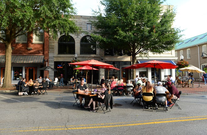 Diners are shown at downtown Spartanburg's Morgan Square July 9.
