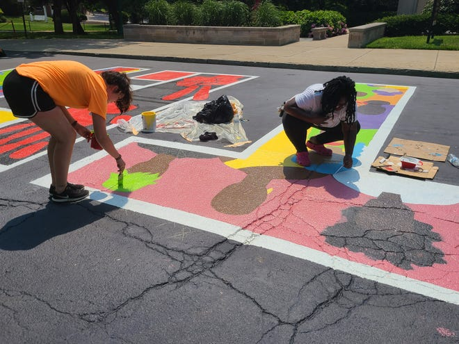"""Olivia Roath and Tiera Howleit work on the last T of """"Black Lives Matter."""" This letter has images representing the diversity of women."""