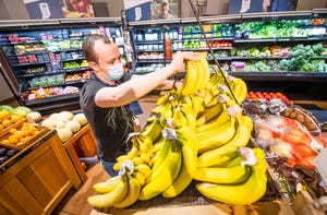 Eric Schurr stocks bananas Friday at Bloomingfoods Near West. The local member-owned food co-operative has done well financially over the past year, despite the pandemic and recent flooding at this store.
