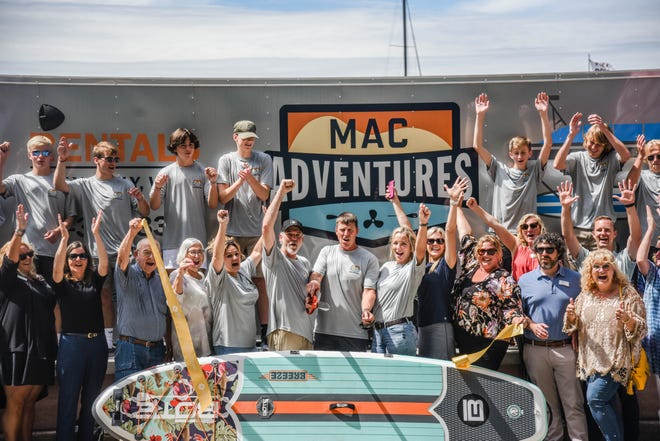 Mac Adventures celebrates its ribbon cutting at Eldean Shipyard in Holland. The business rents stand-up paddle boards, pontoons, tritoons and kayaks.