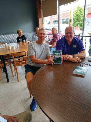 Zack Stamp (right) shares a copy of his new book with Gordy Taylor. Stamp, a native of Stronghurst and former WIU trustee, was in the area to promote his book and see old friends.