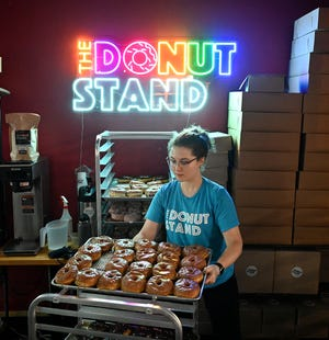 Leah Minnucci puts out the donuts as she prepares for the morning rush at the Donut Stand inside The Vin Bin cafe in Soutboro. After months of pop ups, the shop reopened in May for three days a week. Outside, a line was forming ahead of the 9:00 a.m. opening time.