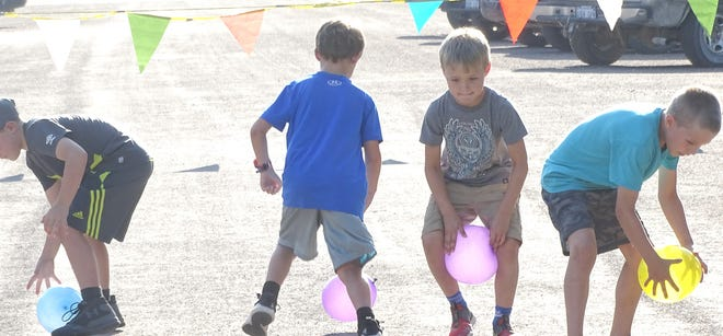 These boys attempt to control the balloons in the balloon race. The racers had to hold balloon between the legs while running the race.