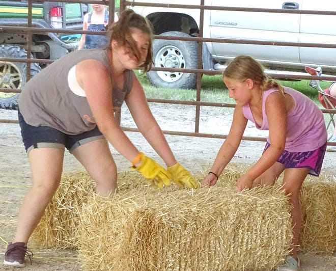 A long tradition at the Richmond Free Fair is the Cowboy Olympics, which was started by George A. Stienberger. These girls team up to move the hay across the arena in the timed event.