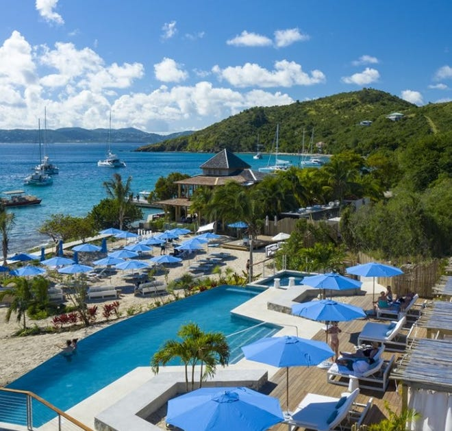 Caribbean-blue umbrellas echo the color of the sea at the Lovango Resort and Beach Club on an island off St. John in the U.S. Virgin Islands.